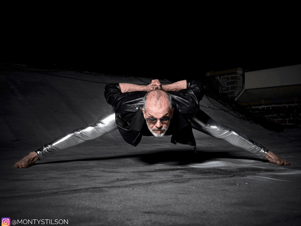 Older man in silver meggings doing splits stretching