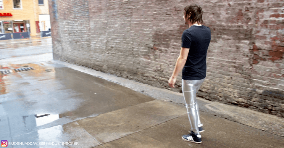 long hair guy wearing black t shirt and silver leggings in street