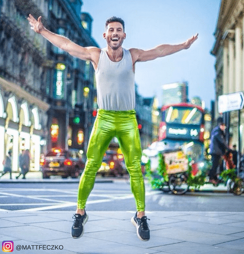 man jumping in green metallic meggings on london street