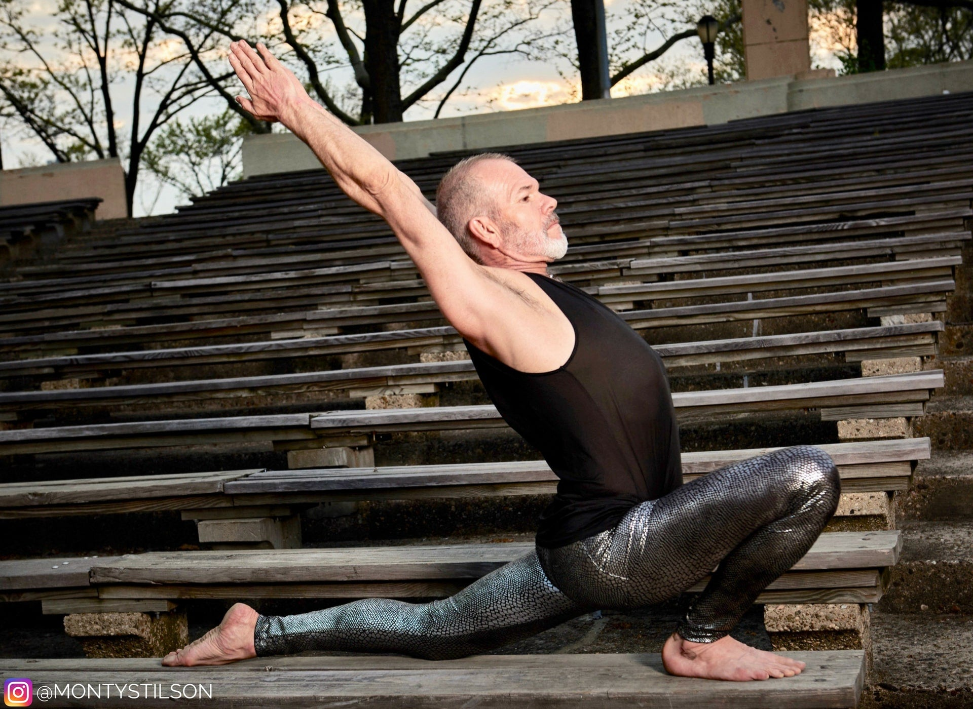 man wearing silver snakeskin leggings in yoga pose