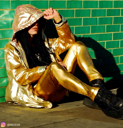model wearing shin gold leggings and gold reflective jacket against green wall