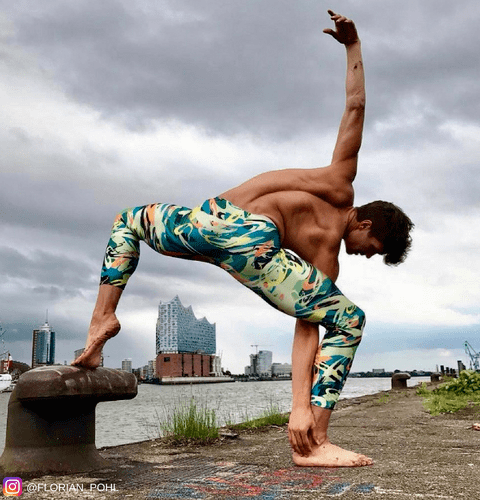 yoga man stretching near river wearing graffiti male leggings