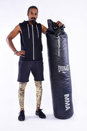 Man in sports pose wearing Kapow Meggings Bengal leopard print men's leggings with boxing bag
