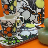 Marimekko Pala Taivasta patterned products in white, green, orange and yellow at Indish Interiors