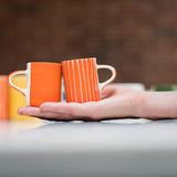 Ceramic espresso cups in tangerine stripes and wash