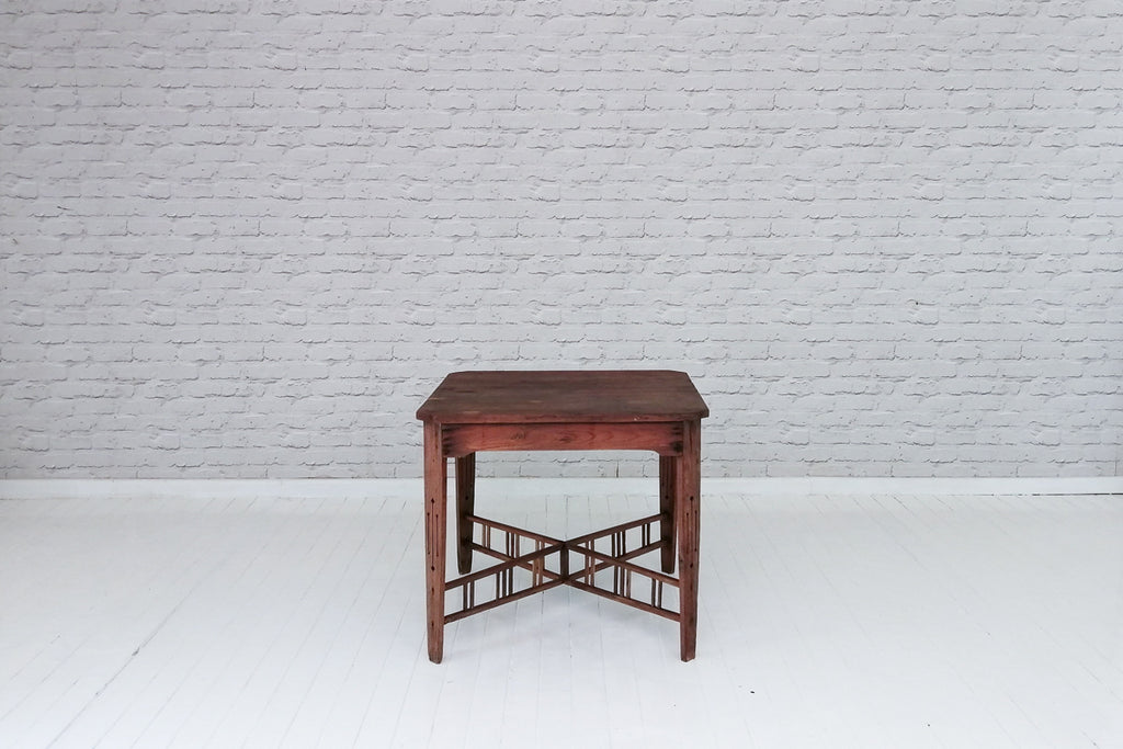 A beautiful vintage teak dining table with galleried X-frame stretcher