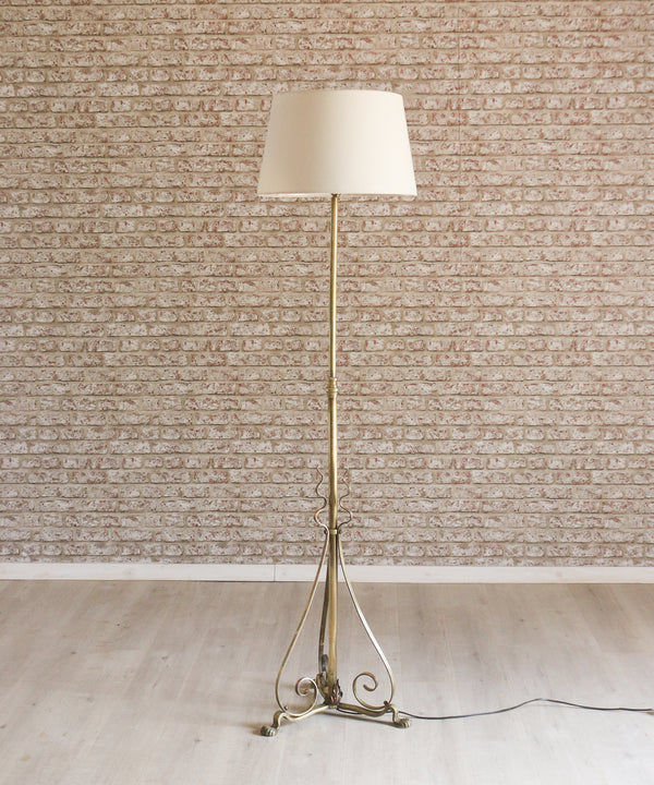 An ornate vintage tripod brass floor lamp with cream shade