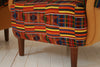 A pair of 1930s armchairs re-upholstered in vintage Ghanian Kente cloth  with yellow cotton side panels