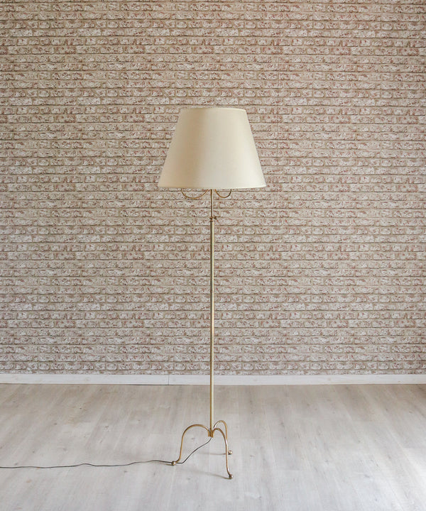 A delicate vintage tripod brass floor lamp with cream shade