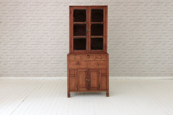 An antique glass fronted Javanese teak cabinet