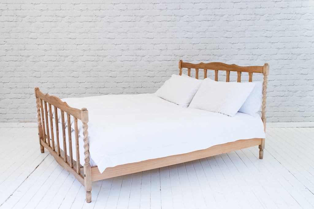 A VINTAGE OAK DOUBLE BED WITH BARLEY TWIST POSTS