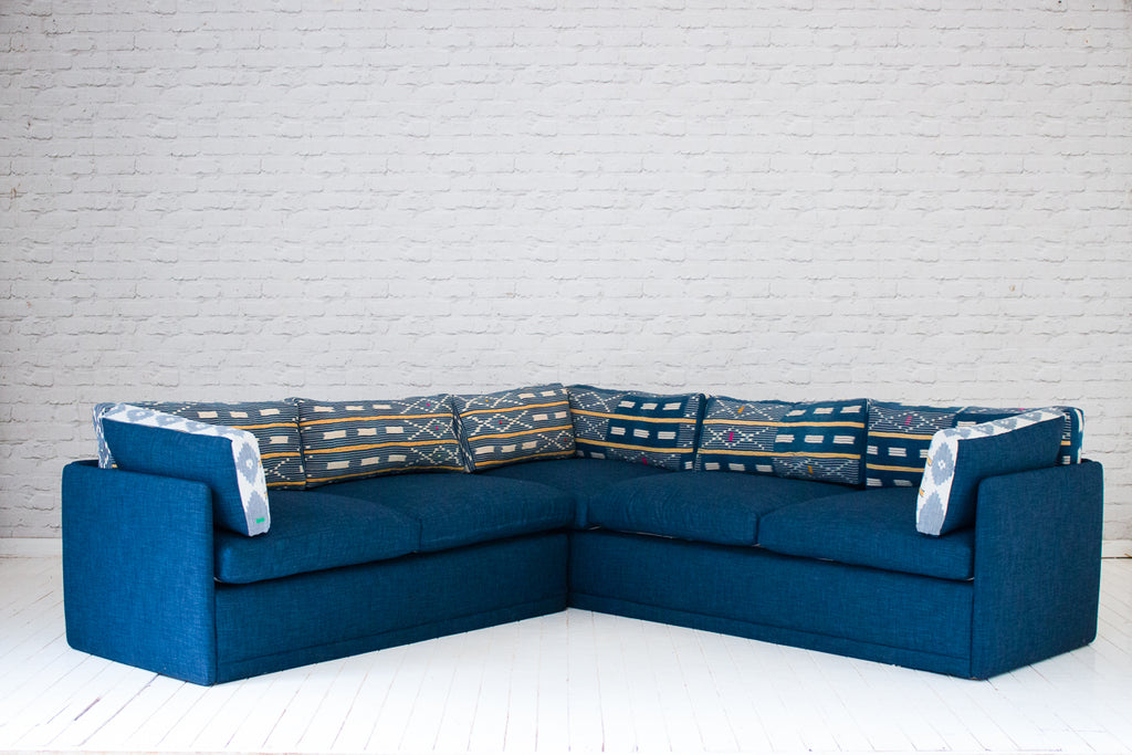 A 1970s L-shaped sofa with indigo upholsetry & vintage Baule cloth back cushions