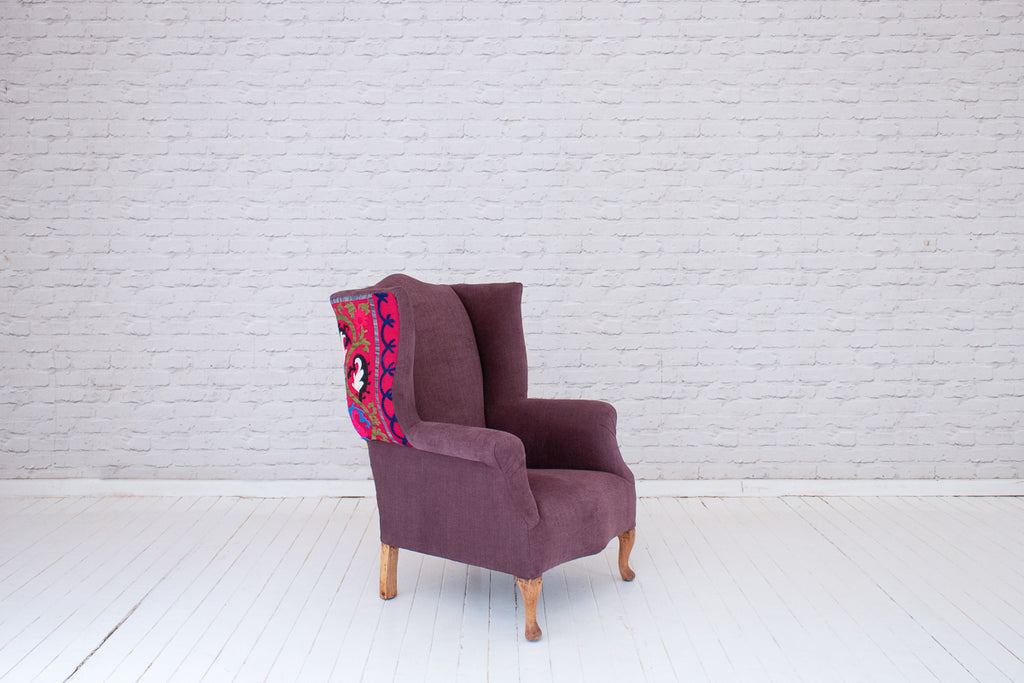 A vintage Georgian style wingback armchair in purple cotton and hand embroidered Suzani