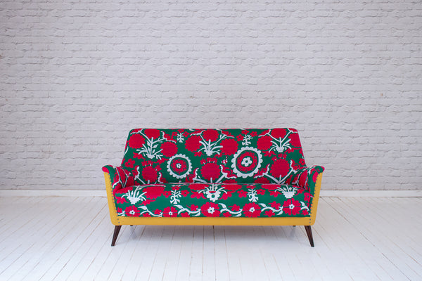 A 1960s cocktail sofa upholstered in vintage Suzani