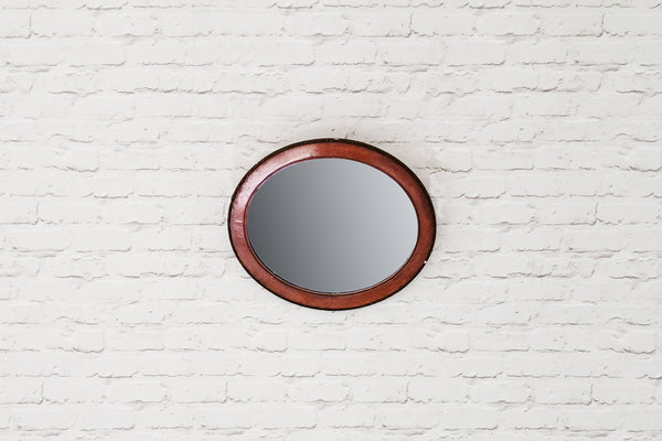 An antique oval mahogany mirror
