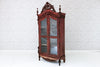 An antique ornately carved glass fronted Javanese teak cabinet