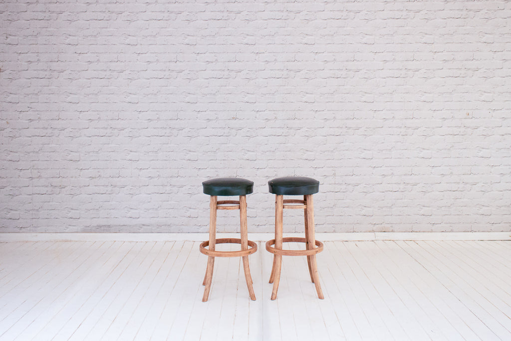 A pair of antique French bistro bar stools with original faux leather seats