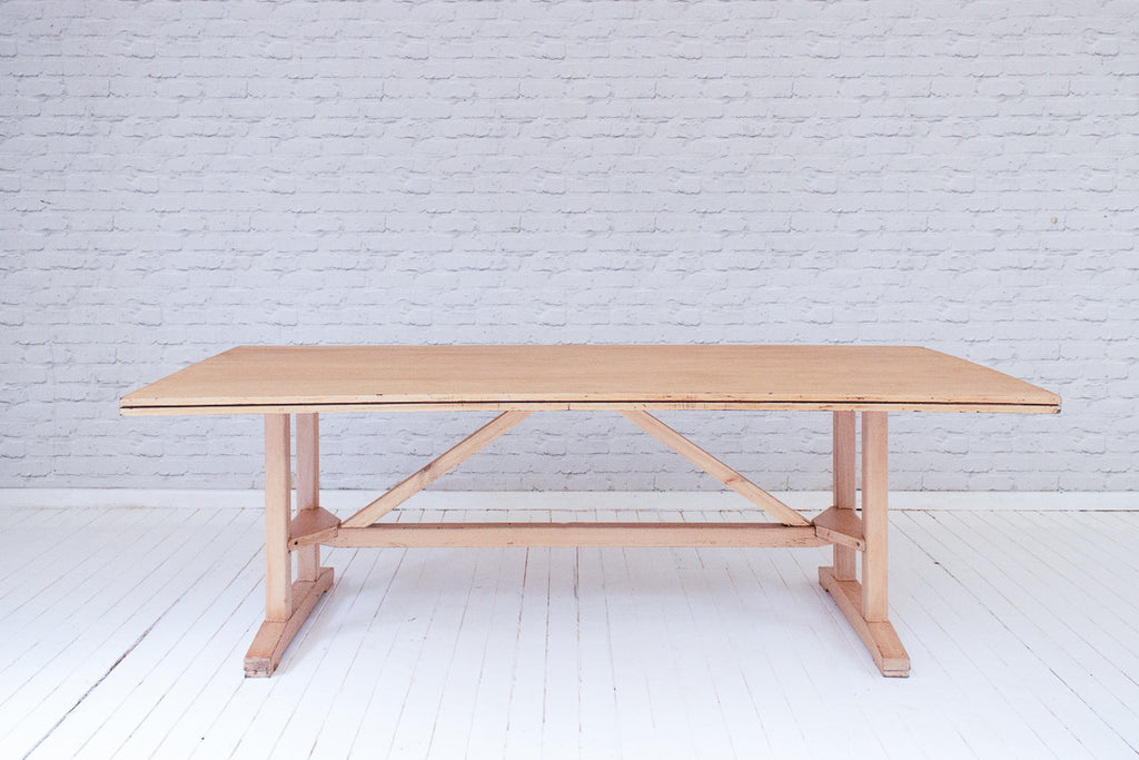 A large vintage dining or meeting table with trestle base