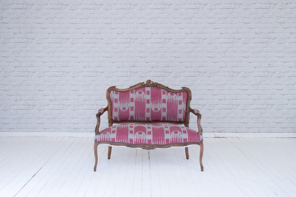 A exquistely carved Louis XV antqiue French oak sofa upholstered in hand printed linen by Alef Gallery, Cairo