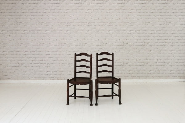 A pair of 18th Century Shropshire ladder back elm seated dining chairs