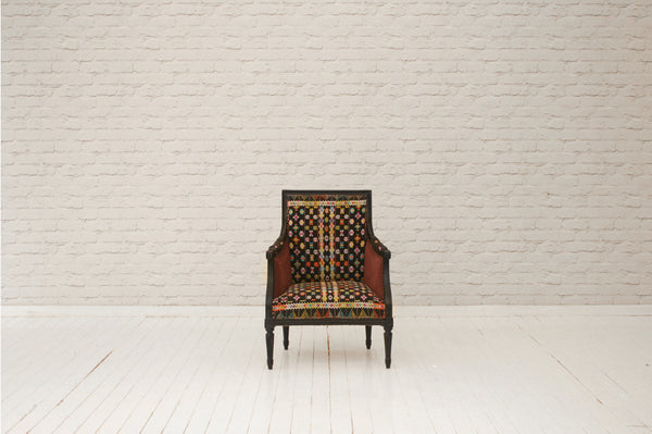 A carved French armchair in vintage Indonesian embroidered sarong