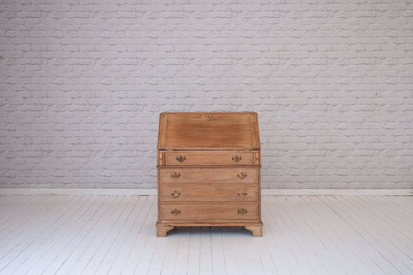 An antique English oak bureau with four drawers