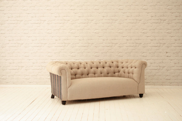 A Victorian button backed chesterfield in cream linen with Turkish cotton striped side & back panels
