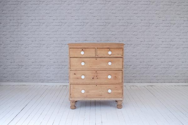 A Victorian English pine cottage chest of drawers with ceramic handles