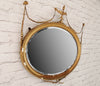 A vintage gilt oval mirror with urn and swag decoration