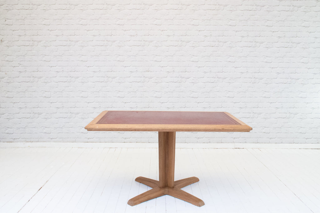 A vintage oak and leather top work table