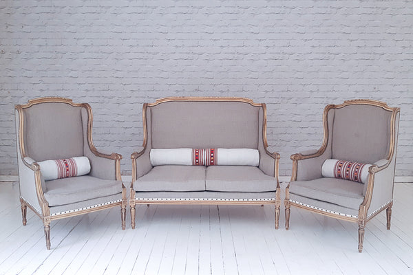 A gilded French sofa set upholstered in Lithuanian linen with hand-embroidered Hungarian bolster cushions