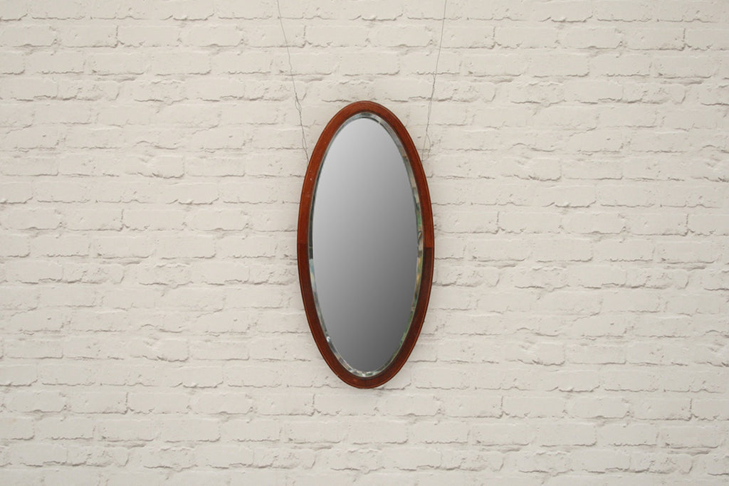 An vintage oval mahogany wall mirror