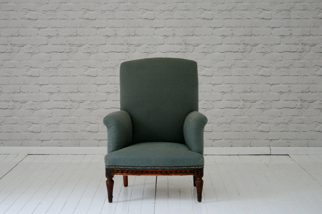 An early 1900s carved oak framed armchair in grey Volga linen