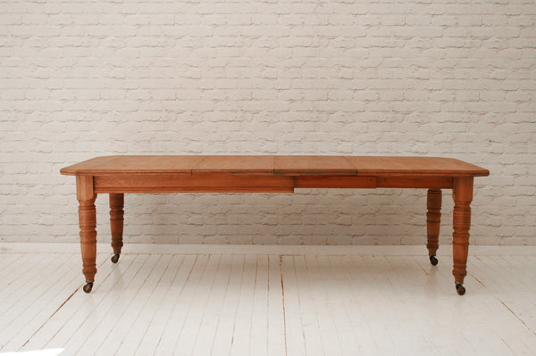 A large Victorian oak dining table with two extra leaves