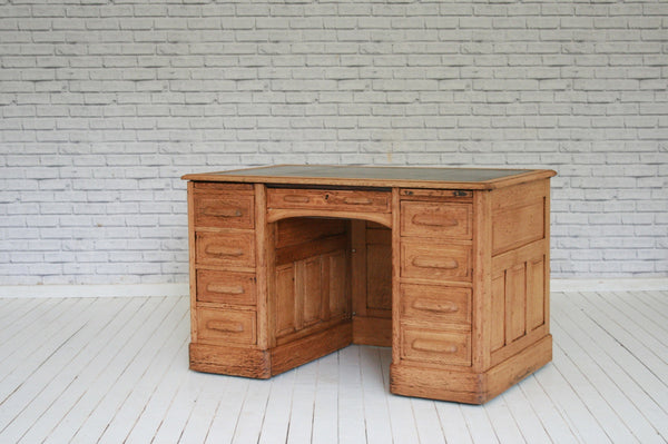 1930's panelled oak knee hole desk with green leather insert top