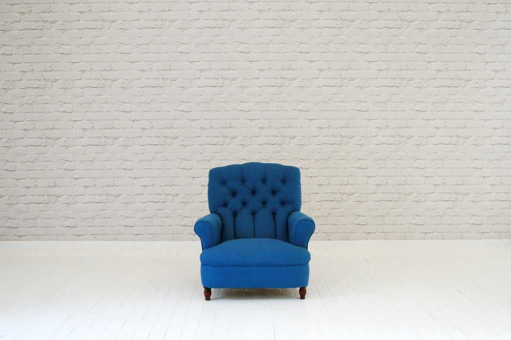 A Victorian button backed armchair in blue cotton and indigo cloth