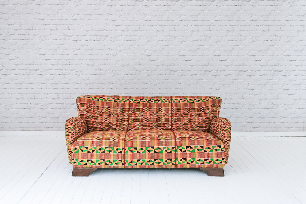 An Art Deco (1925-1940) sofa upholstered in vintage West African Kente cloth & crimson linen