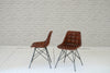 A set of four distressed leather & aluminum dining chairs