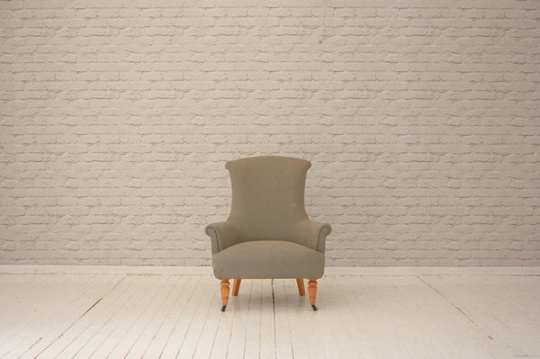 A contemporary armchair in pale grey Volga linen