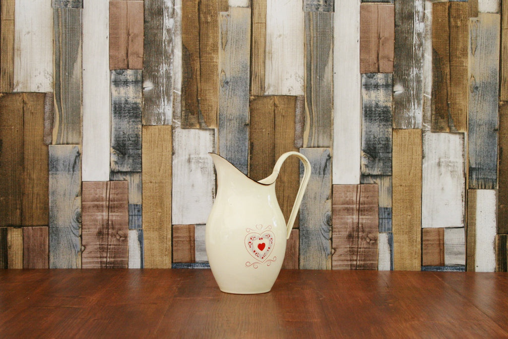 A large cream enamelware jug with love hearts