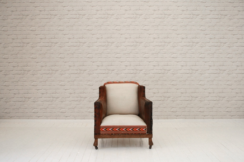 A leather Edwardian armchair with Hungarian sack cloth centre panel