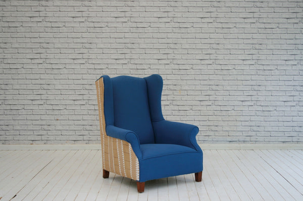 An Edwardian wingback armchair in blue cotton with Asoke side panels