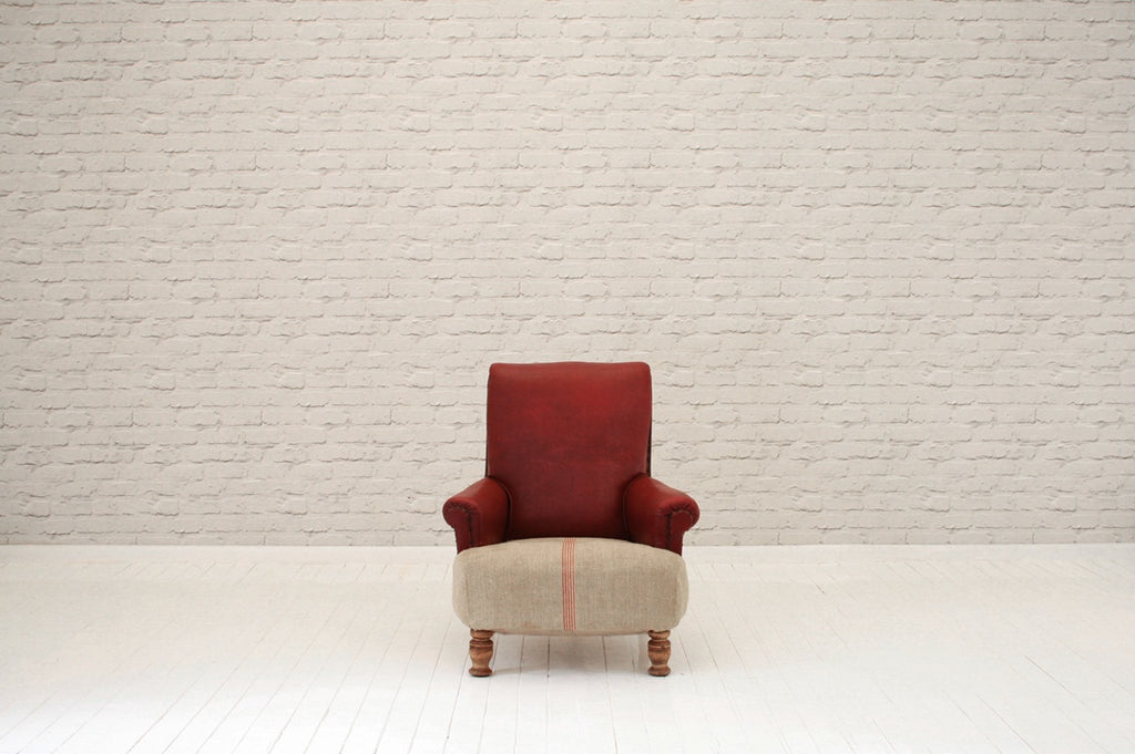 An Edwardian armchair in original red faux leather & Hungarian sack cloth