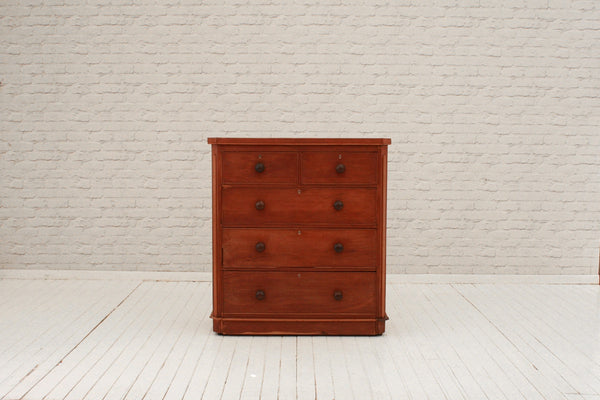A Victorian mahogany two over three chest of drawers with bun handles