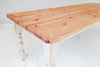 A large partly painted pine kitchen or dining table