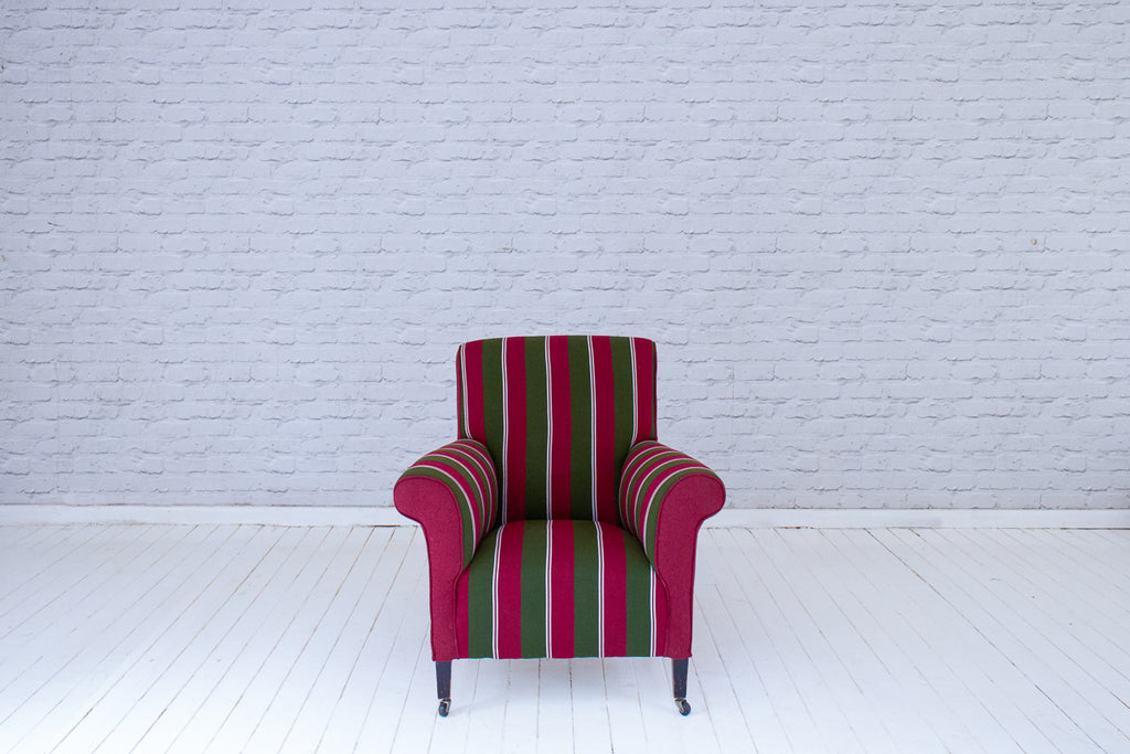 An Edwardian (1890-1910) club chair upholstered in hand woven West African Ewe