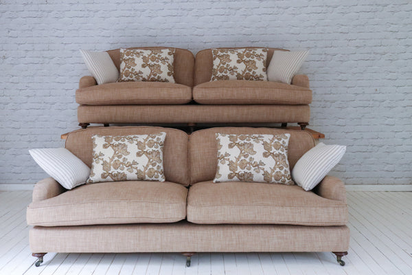 "A pair of English sofas newly upholstered in rich oatmeal cotton with linen ""Fruiting Fig"" cushions by Botanica Trading"