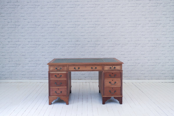 An Edwardian mahogany twin pedestal desk with green gilt leather top
