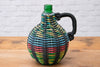 A vintage Hungarian storage bottle with woven cover