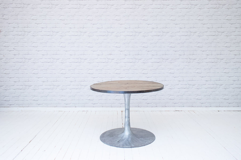 An vintage industrial table with a metal bound pine top on a polished metal base